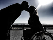 Young-woman-in-wheelchair-kissing-her-boyfriend-silhouetted-against-the-sun