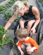 Mother-in-wheelchair-picking-strawberries-with-her-son