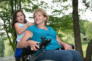 Grandmother-using-power-wheelchair-in-park-with-her-granddaughter