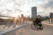 Young-woman-in-wheelchair-exploring-coastal-city-park-on-sunset
