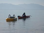 Woman-kayaking-on-mountain-lake-towing-her-wheelchair
