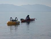 Woman-kayaking-on-mountain-lake-towing-her-wheelchair