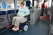 Woman-sitting-on-bus-in-designated-area-for-wheelchair-users-looking-out-the-window,