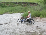 Man-in-an-off-road-handcycle-fishing-in-mountain-stream