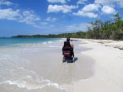 Man-in-power-chair-on-beautiful-white-tropical-ocean-beach