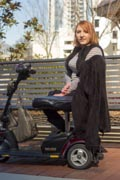 Woman-sitting-on-park-bench-with-her-mobility-scooter