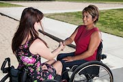Two-woman-using-wheelchairs-meeting-in-park