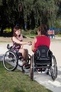 Two-women-using-wheelchairs-meeting-in-park
