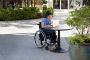 A-young-woman-using-wheelchair-using-laptop-at-sidewalk-cafe