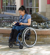 A-young-woman-using-wheelchair-reading-book-by-fountain