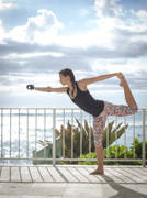 Young-woman-with-prosthetic-arm-exercising-in-tropical-setting-overlooking-the-ocean