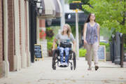 Young-woman-using-wheelchair-on-city-sidewalk-with-her-friend