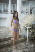 Young-woman-in-bikini-walking-down-her-apartment-steps