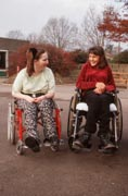 Two-teenage-girls-with-disabilities;-who-wheelchair-users;-talking-together-in-playground,