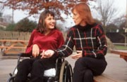 Teenage-girl-with-disability;-who-is-wheelchair-user;-talking-to-teacher,