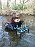 Young-man-on-an-offroad-handcycle-in-river-with-his-dog