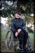 Young-woman-in-wheelchair-in-leather-jacket-in-park