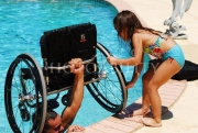 Man-handing-his-daughter-his-wheelchair-from-the-swimming-pool
