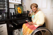 Woman-using-wheelchair-on-the-phone-in-front-of-her-computer