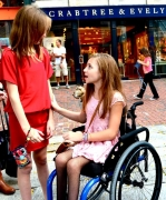 Young-girl-in-wheelchair-in-city-street-with-her-friend