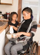 Young-mother-in-wheelchair-cooking-with-her-daughter