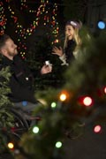 Man-in-wheelchair-proposing-to-his-girlfriend-in-front-of-Christmas-Tree
