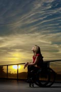 Woman-in-wheelchair-on-balcony-at-sunset