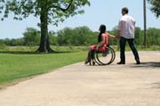 Young-woman-in-wheelchair-in-park-with-her-boyfriend