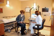 Woman-in-wheelchair-in-an-examination-room-with-her-doctor