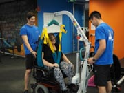 Two-Male-Physical-Therapists-Giving-Treatment-To-A-Woman-With-A-Disability