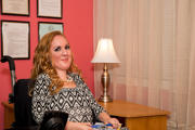 Young-professional-woman-in-wheelchair-at-work-in-an-office