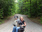 Young-woman-using-power-wheelchair-on-forest-road-with-her-dog