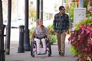 Young-woman-in-wheelchair-on-city-sidewalk-out-shopping-with-her-boyfriend.